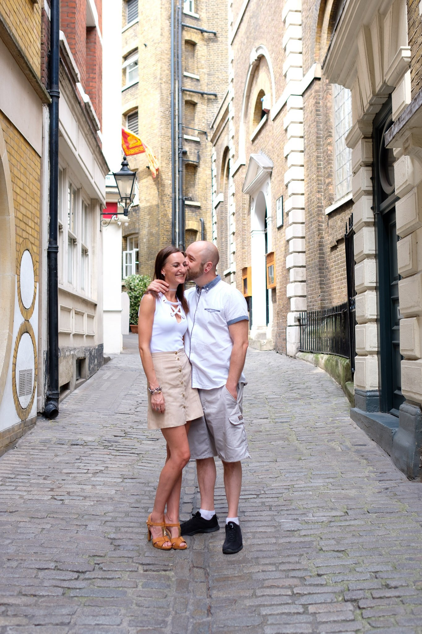 Engagement portrait of kissing couple on cobbled street in London