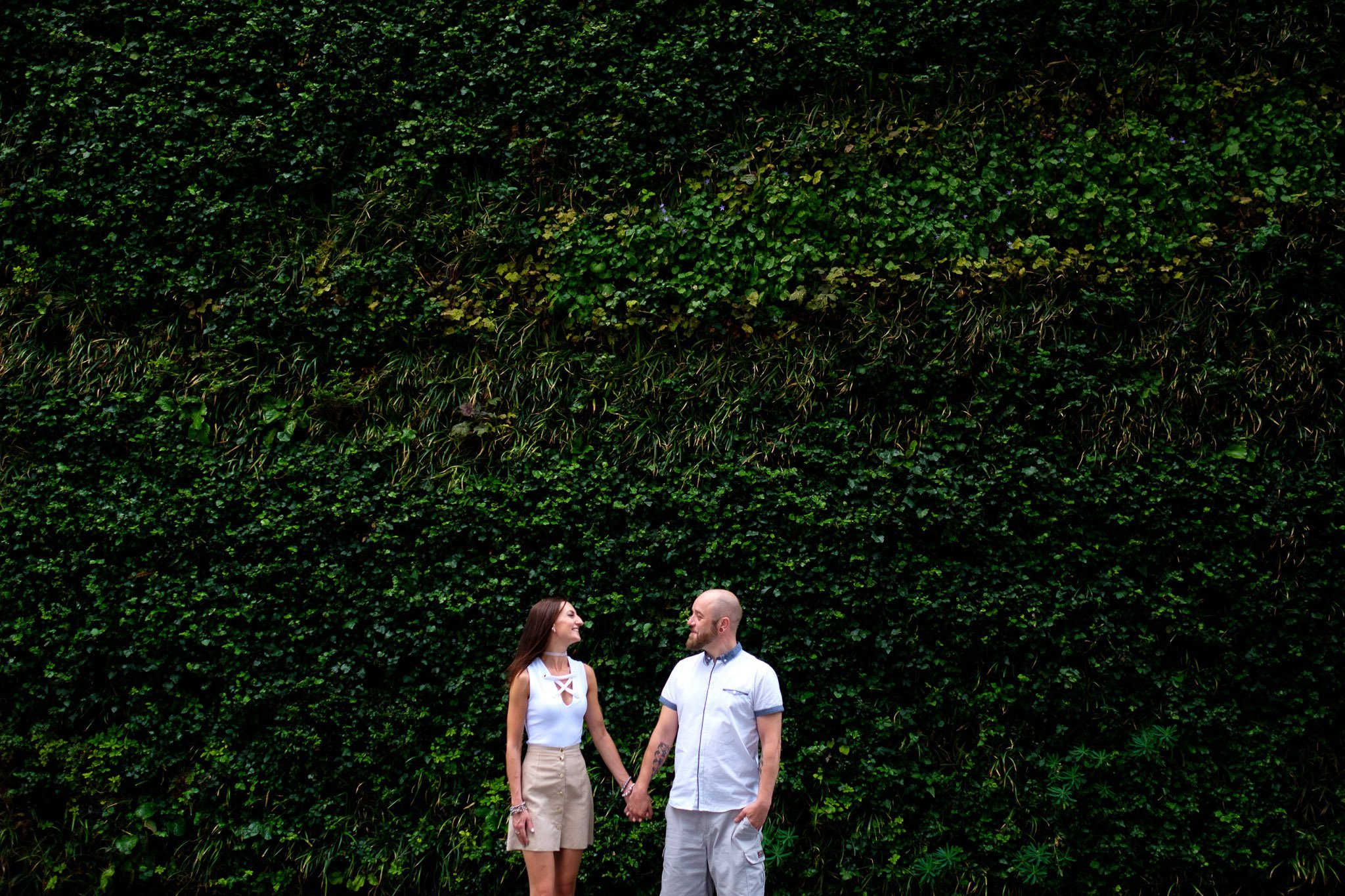 Engagement portrait of couple holding hands in front of wall of grass