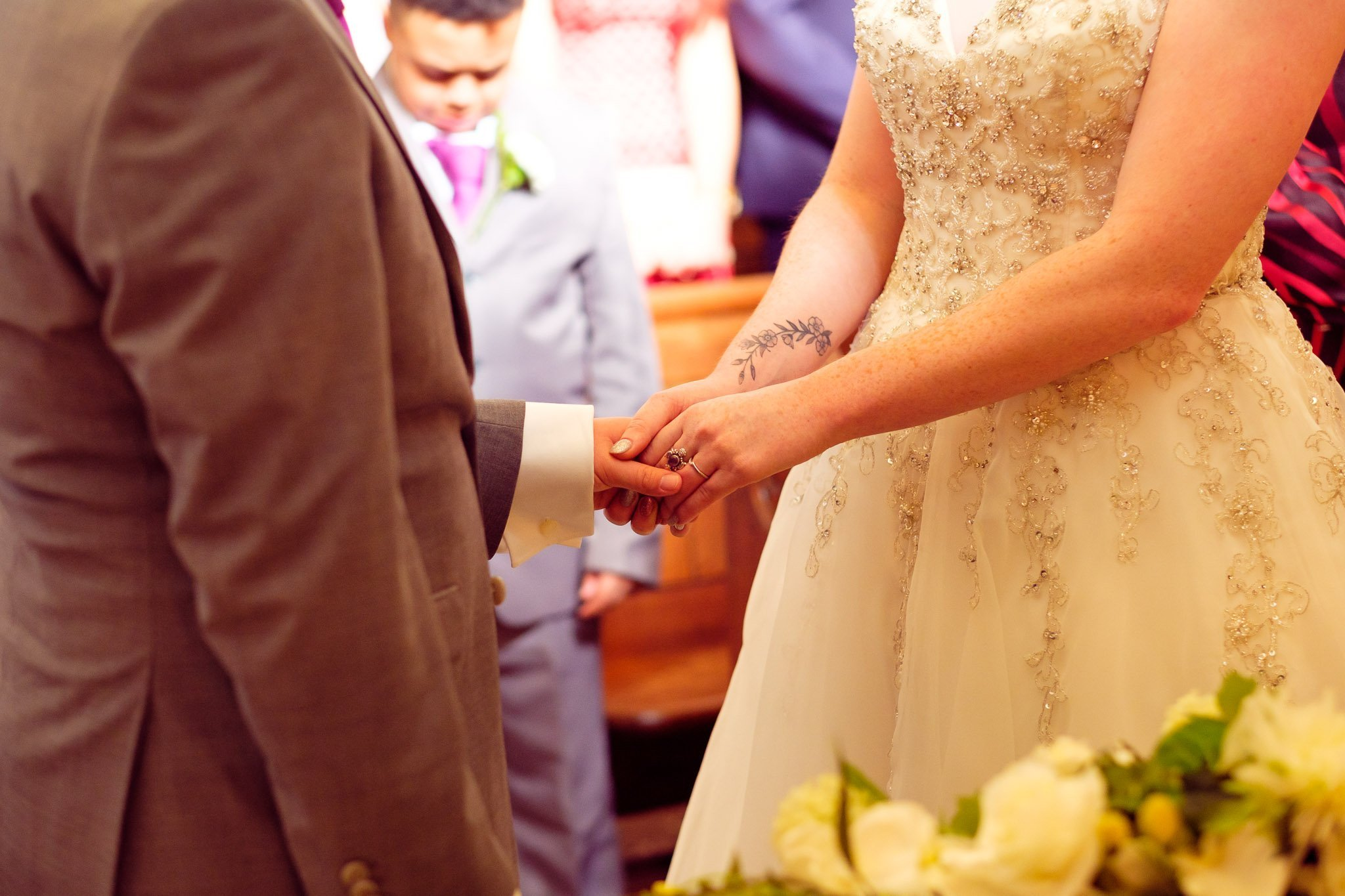 Close up of bride and groom holding hands at wedding ceremony at The Chapel at Orsett Hall Hotel Essex Wedding