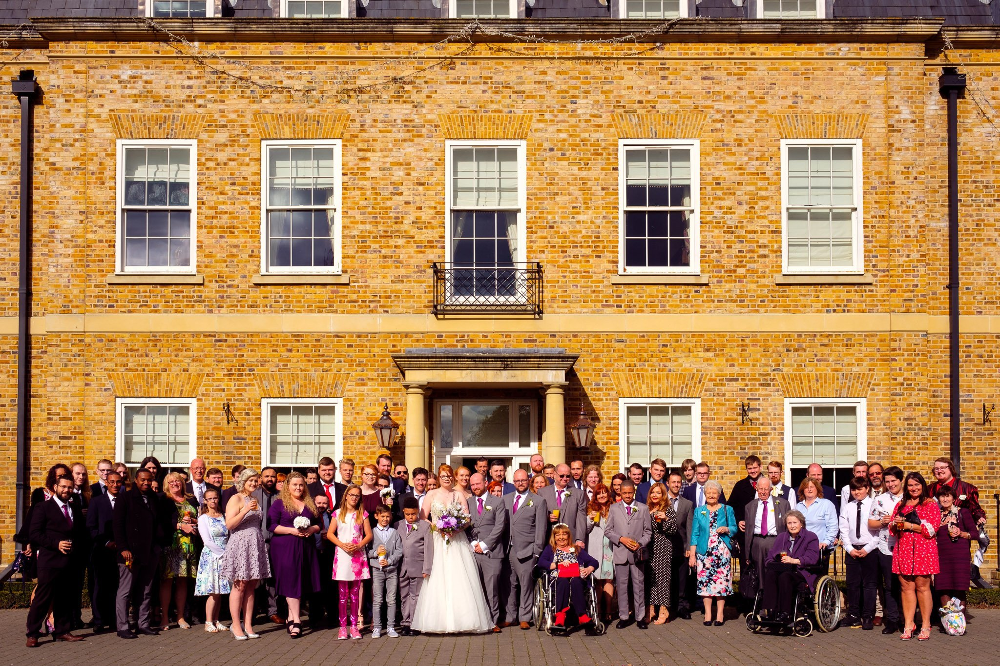 Large group shot of wedding guests outside Orsett Hall Hotel Essex Wedding