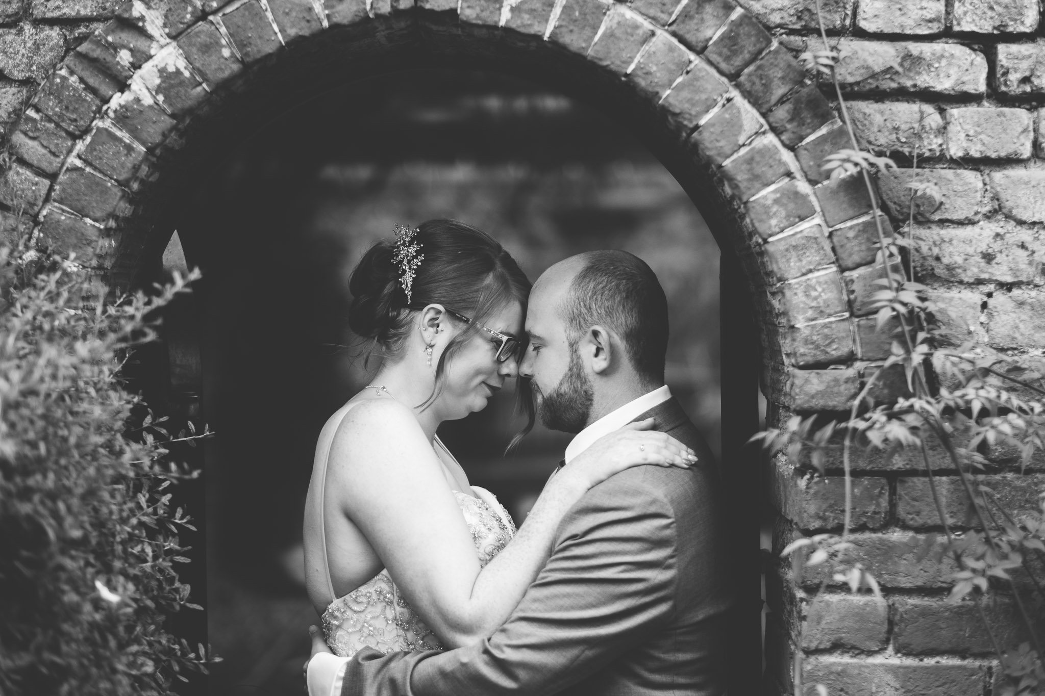 Bride and groom portrait under a brick arch at Orsett Hall Hotel Essex Wedding