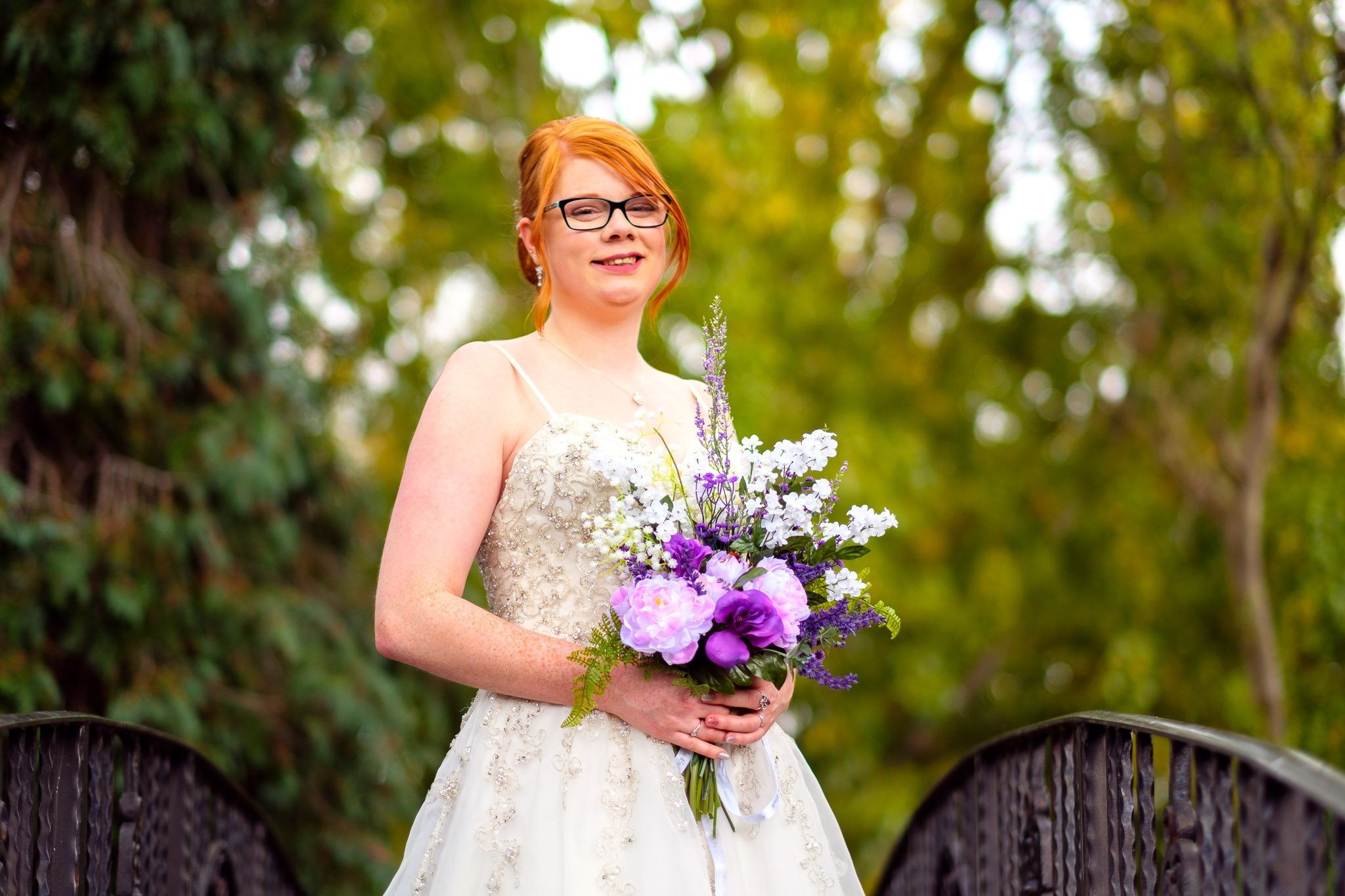 Bride holding a bouquet on a bridge at Orsett Hall Hotel Essex Wedding