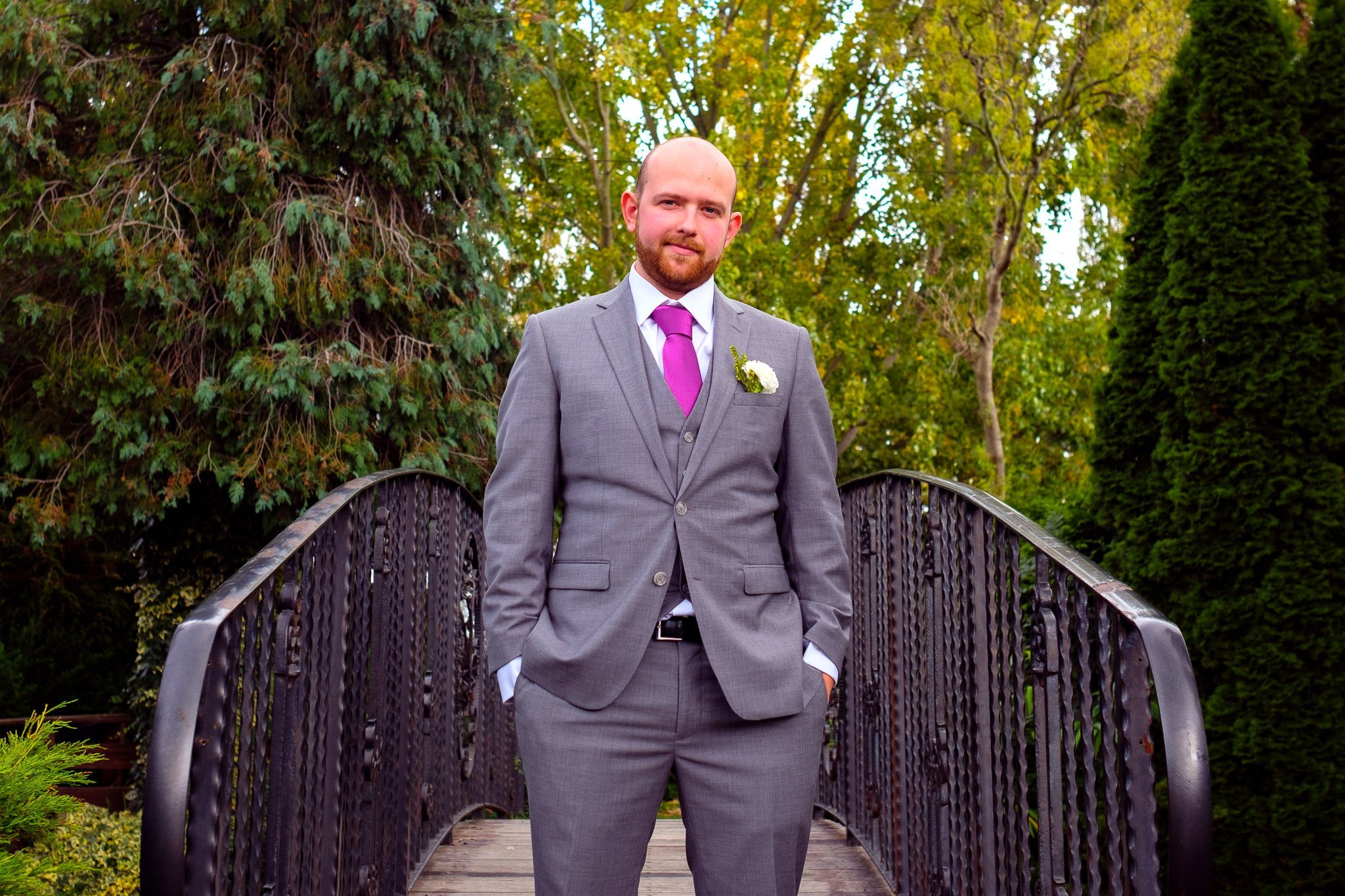 Portrait of groom with hands in pocket on a bridge at Orsett Hall Hotel Essex Wedding