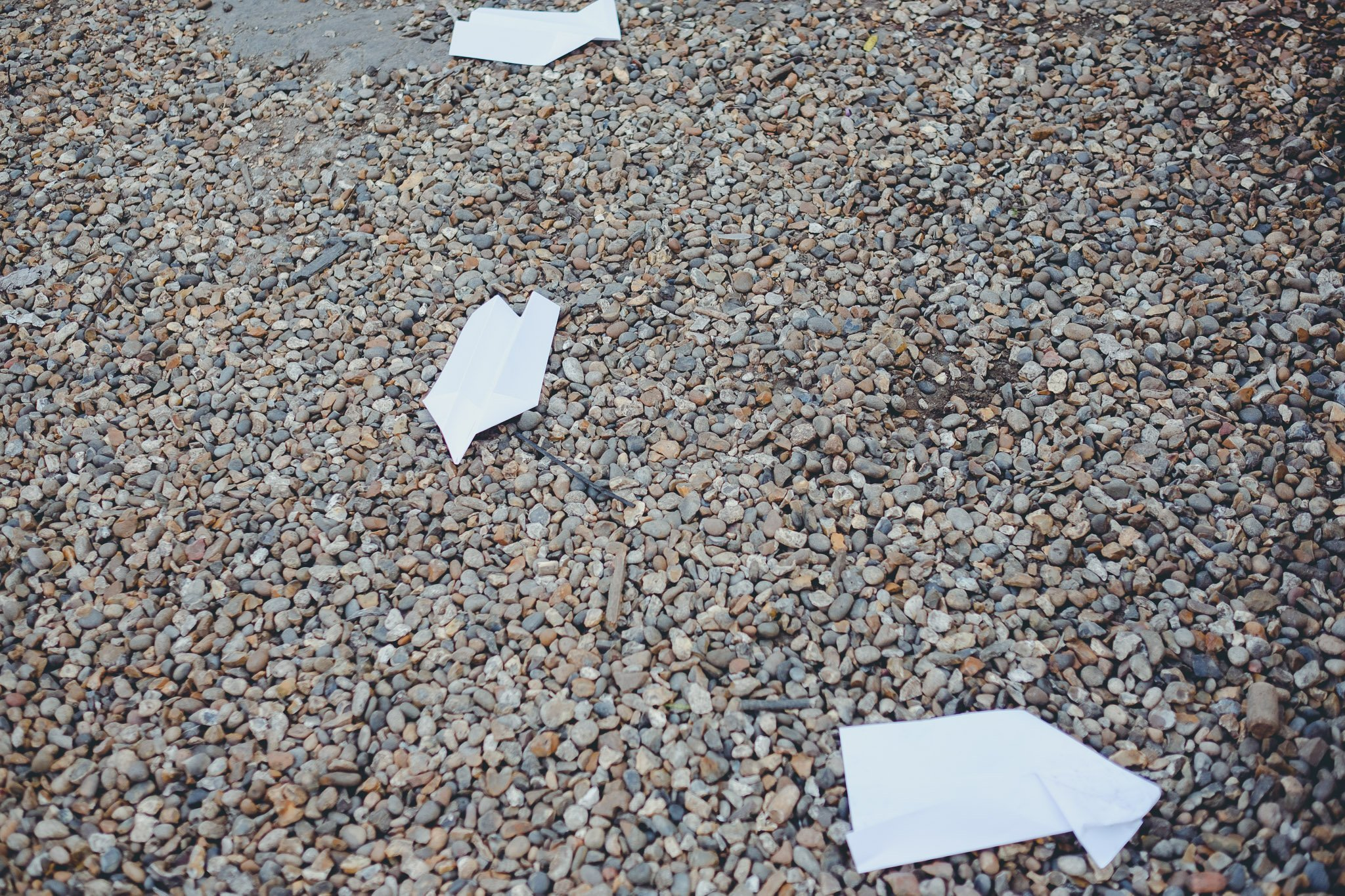 Discarded paper planes on pebbles
