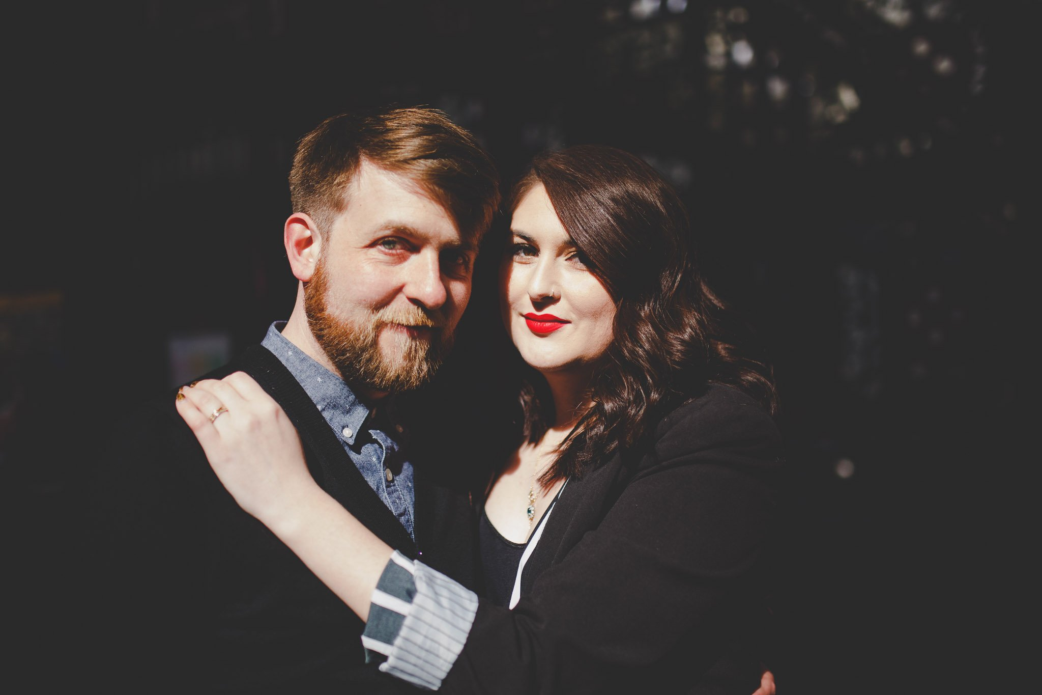 A newly married couple pose for their wedding portrait in Guildhall London. They sit hugging and laughing in front of a stained glassed window. Photography by thatthingyoupluck.
