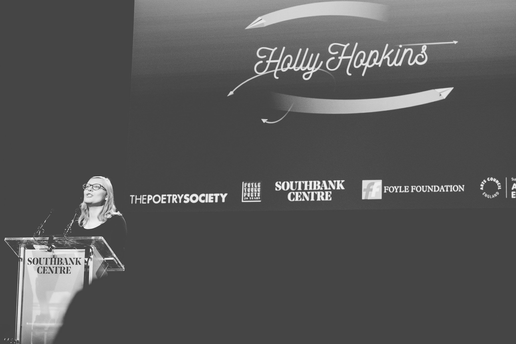 Poet Holly Hopkins on stage reading her poetry at the Southbank Centre London