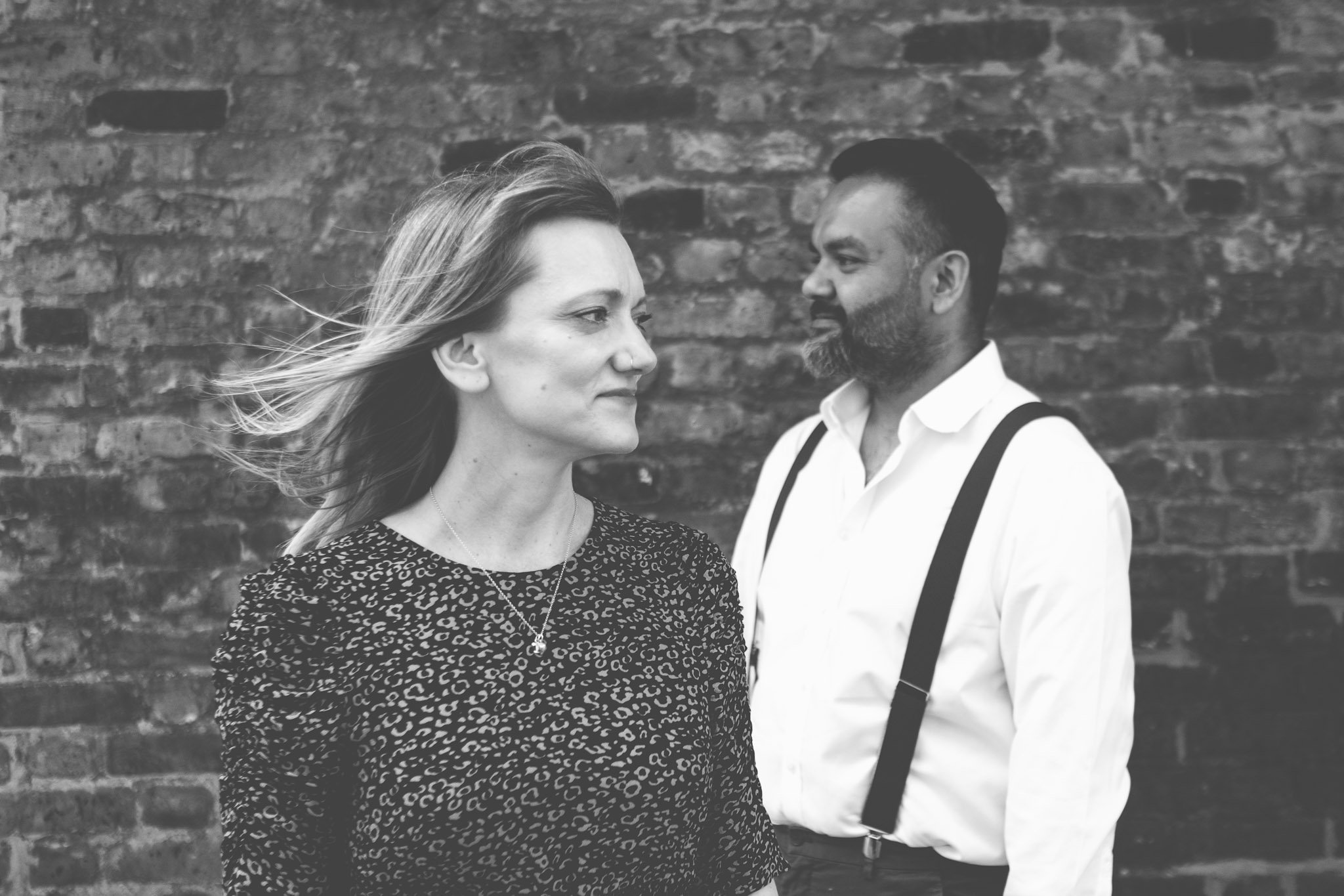 Creative portrait of a couple facing opposite directions in front of a brick wall in London on an engagement shoot. Photography by thatthingyoupluck.