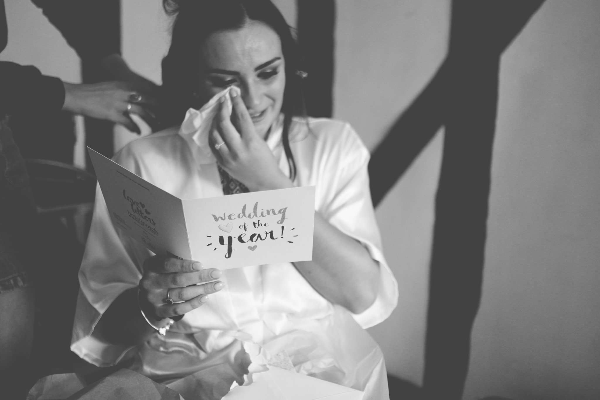 Bride crying while reading a wedding card. Photography by thatthingyoupluck.
