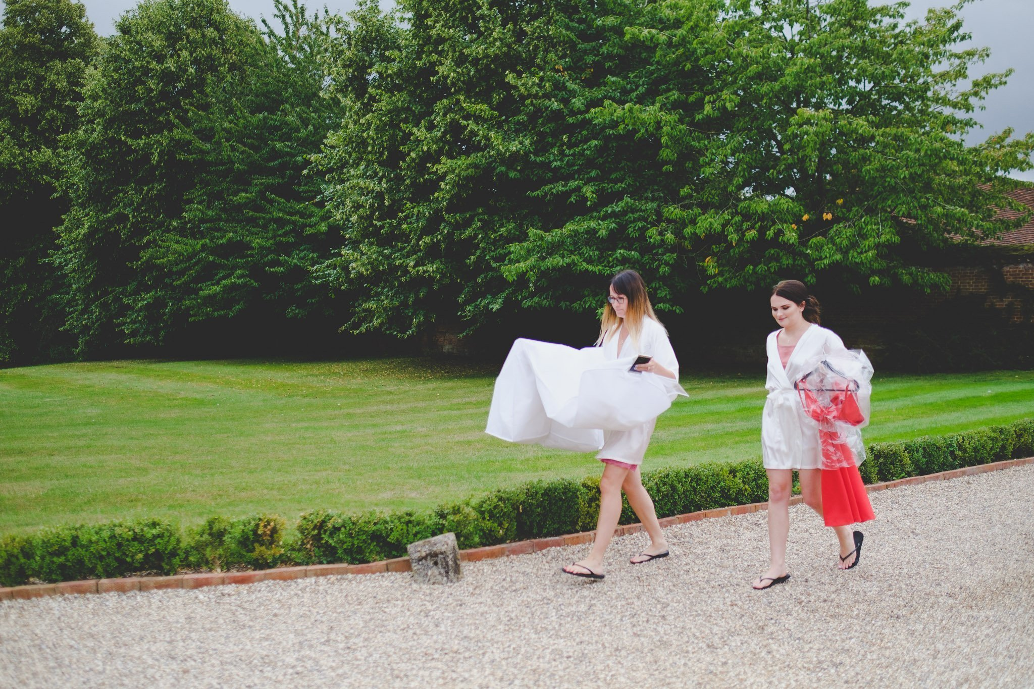 Bridesmaids carrying dresses outside