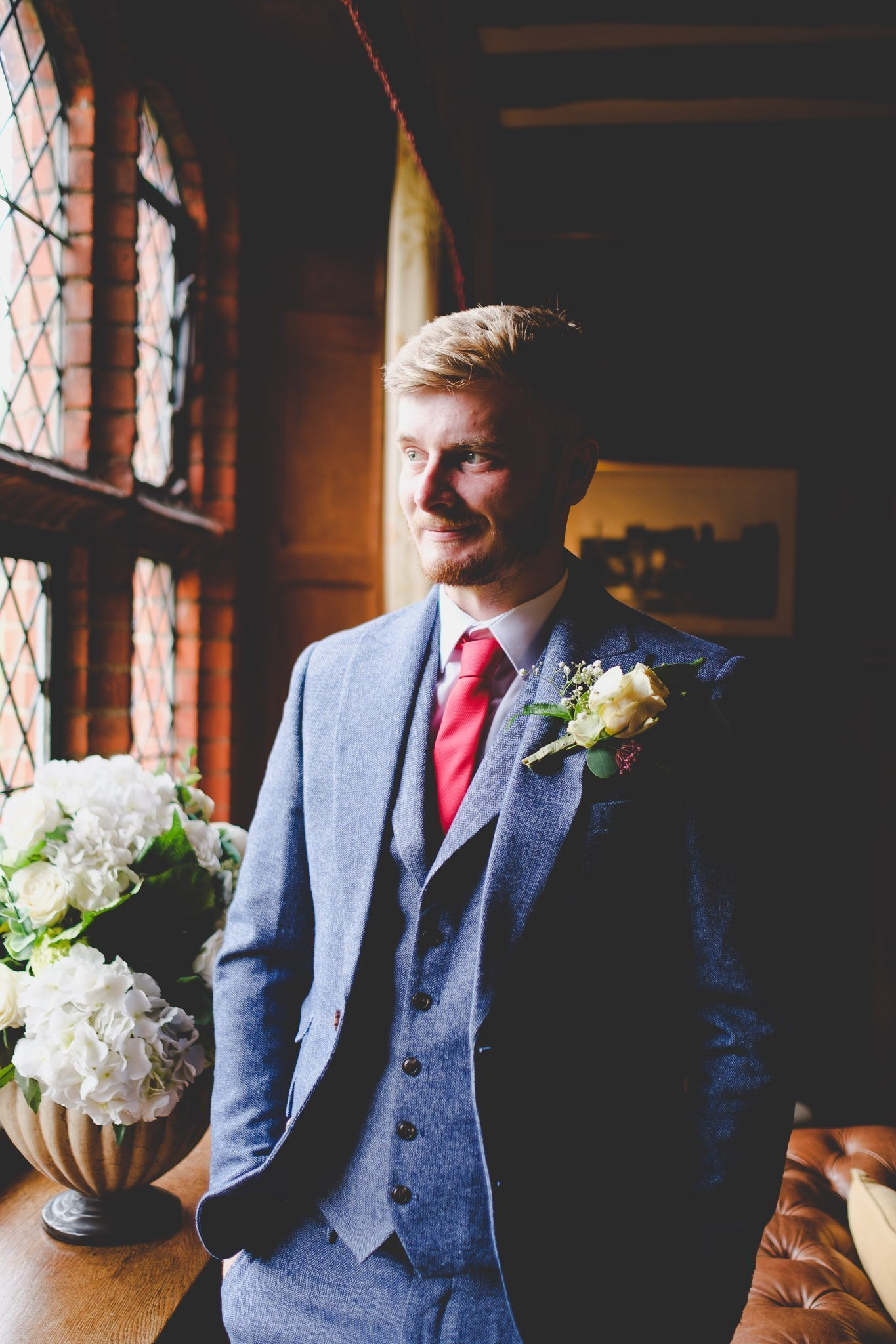 Creative portrait of a groom wearing blue wool three piece suit at Leez Priory Chelmsford wedding. Photography by thatthingyoupluck.