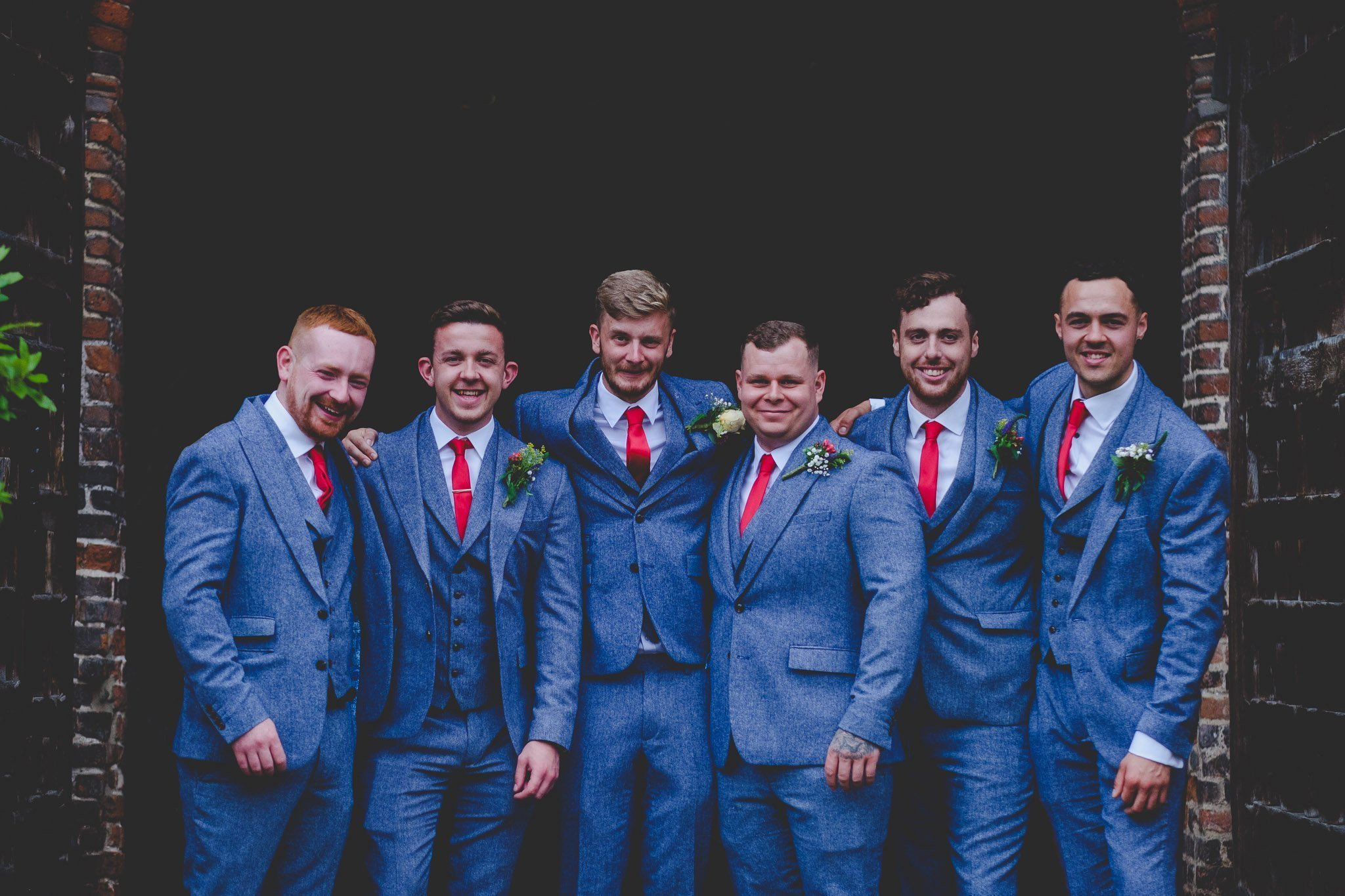 Portrait of groom and groomsmen in blue wool suits with red tie at Leez Priory wedding. Photography by thatthingyoupluck.