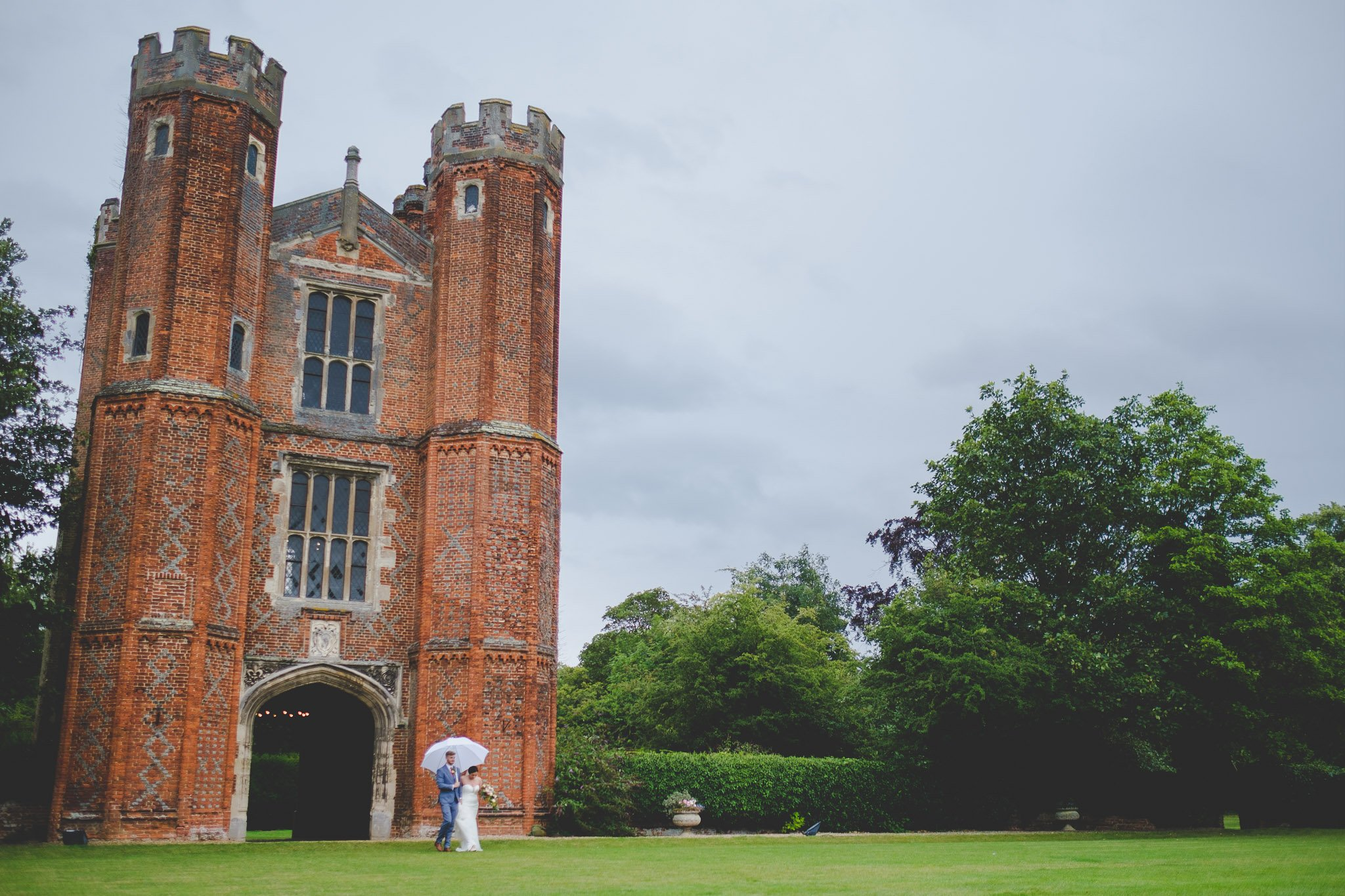 Portrait of a just married couple walking away from the Great Tower at Leez Priory. Photography by thatthingyoupluck.