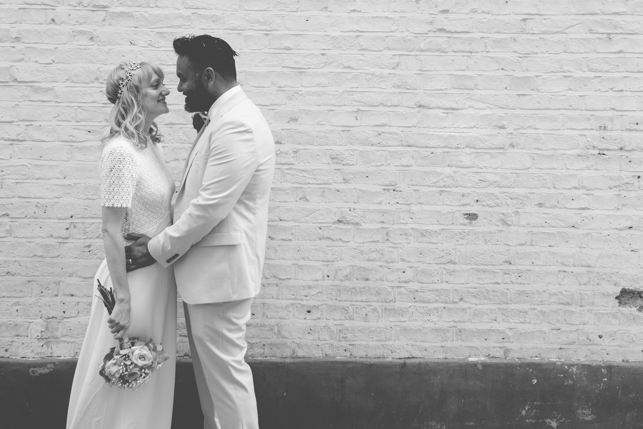 Creative portrait of a bride & groom in front of a brick wall in London. Photography by thatthingyoupluck.