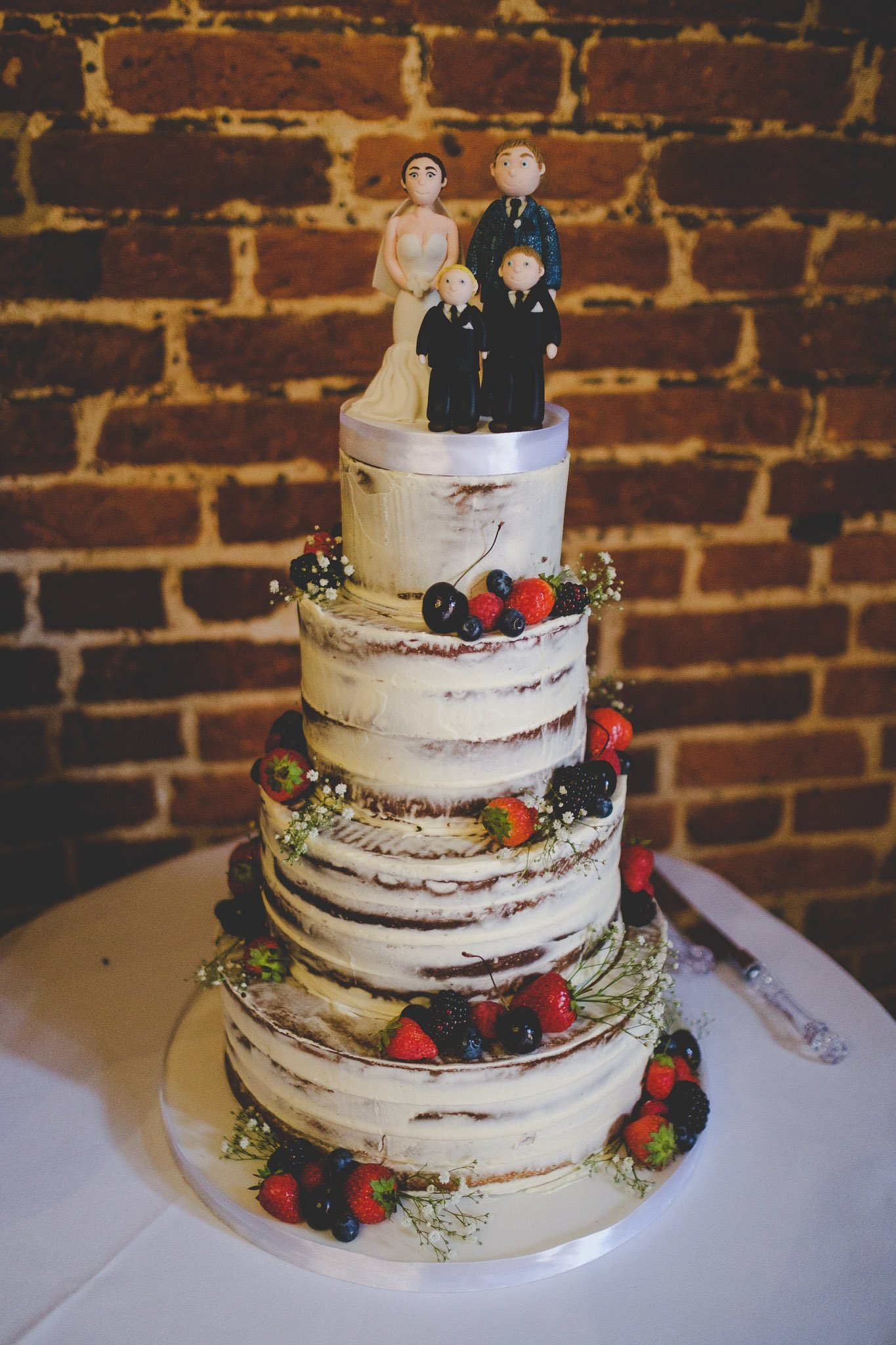 Naked wedding cake with family cake topper. Photography by thatthingyoupluck