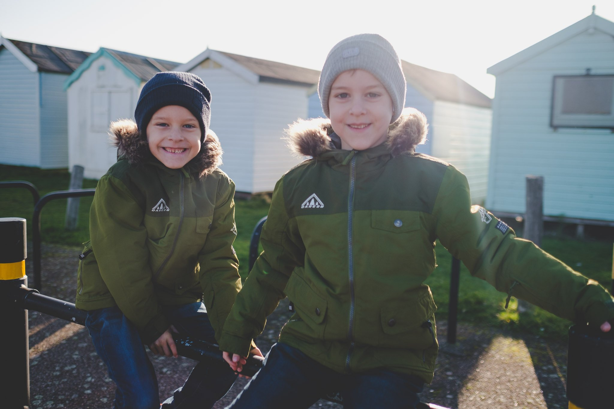 Twin boys sit smiling on a car park railing