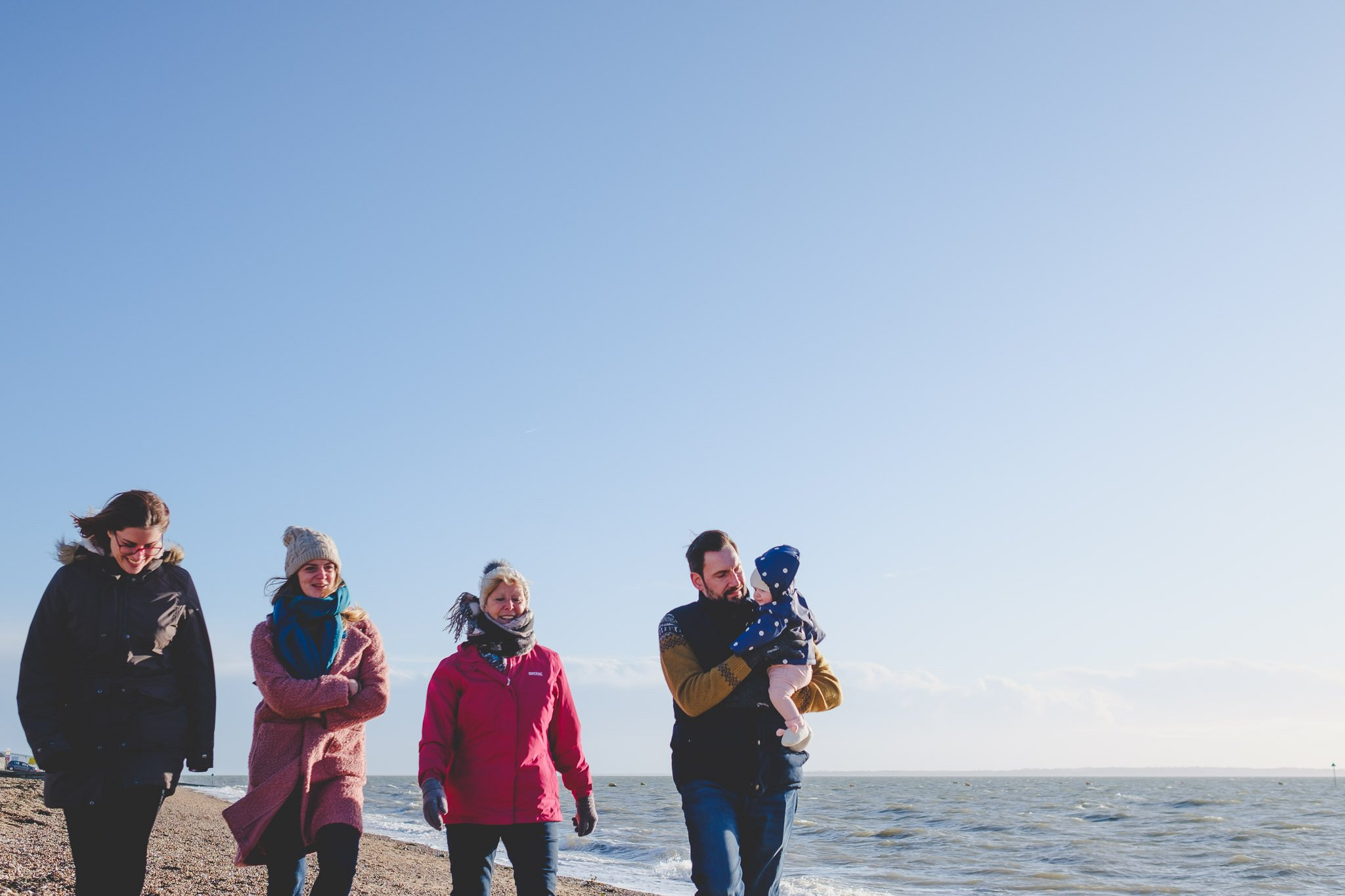 Young family walking along Shoeburyness beach
