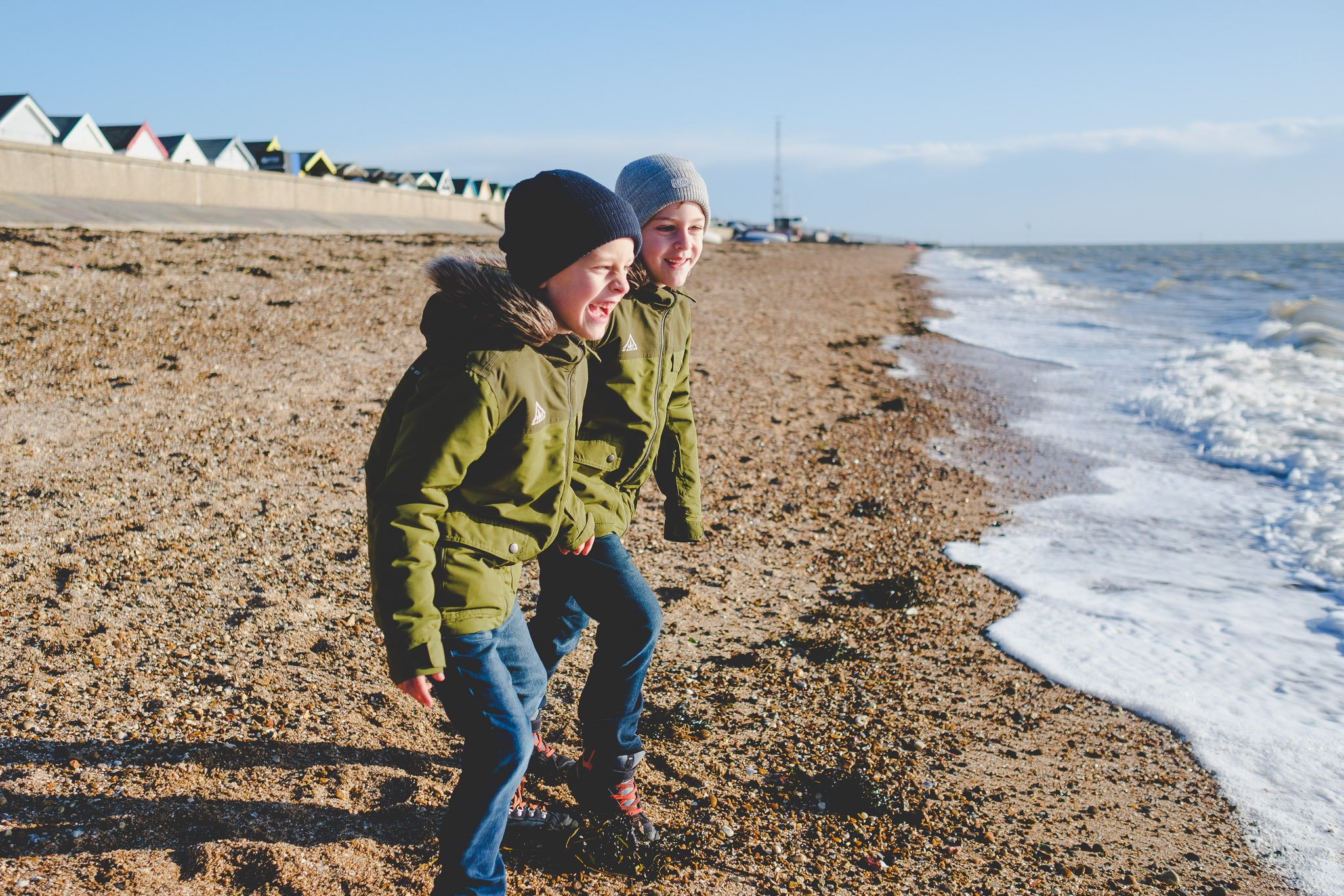 Twins in matching green jackets watching the tide at Shoeburyness beach. Photography by thatthingyoupluck.
